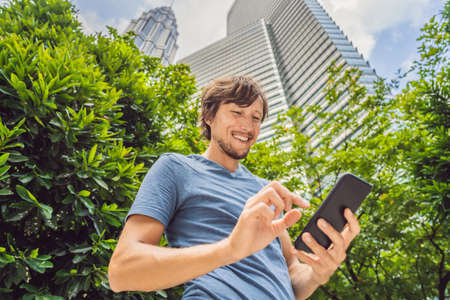 Man Tourist using navigation app on the mobile phone. Navigation map on a smartphone in a big city