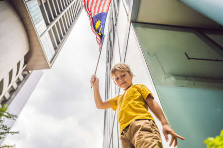 Young boy tourist with the flag of Malaysia near the skyscrapers. Traveling with kids concept Reklamní fotografie