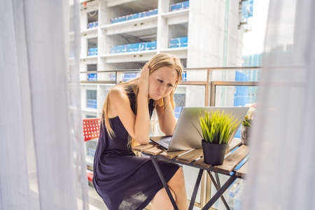 Giovane donna che cerca di lavorare sul balcone infastidita dai lavori di costruzione all'esterno. Concetto di rumore. Inquinamento atmosferico da polvere di edifici