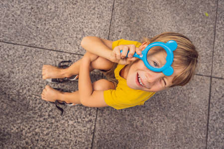 Boy sits on the floor and looks into a magnifying glass