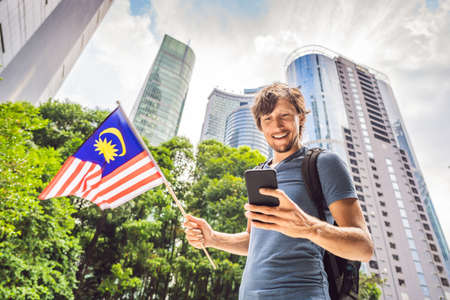 Travel and technology. Young man tourist with the flag of Malaysia is looking at a city map in a smartphone for navigation Reklamní fotografie