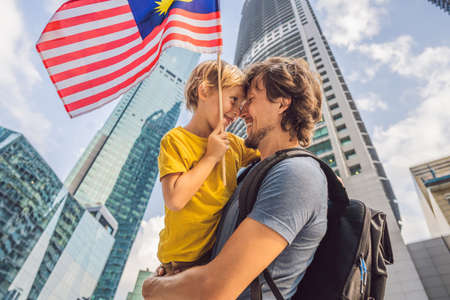 Dad and son tourists in Malaysia with the flag of Malaysia near the skyscrapers. Traveling with kids concept