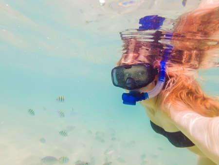 Femme heureuse en masque de plongée sous-marine avec des poissons tropicaux dans la piscine de la mer de corail. Mode de vie de voyage, aventure en plein air de sports nautiques, cours de natation pendant les vacances d'été à la plage Banque d'images