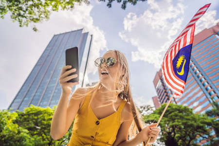 Travel and technology. Young woman tourist with the flag of Malaysia is looking at a city map in a smartphone for navigation Reklamní fotografie