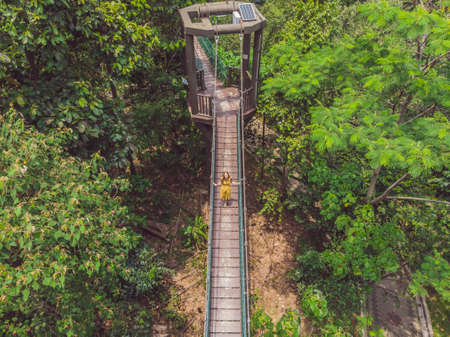 Young woman tourist at capilano suspension bridge kuala lumpur forest eco-park areial view