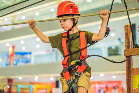Adorable little boy enjoying his time in climbing adventure park in the mall