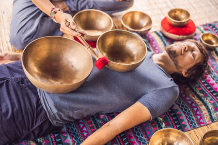 Nepal Buddha copper singing bowl at spa salon. Young beautiful man doing massage therapy singing bowls in the Spa against a waterfall. Sound therapy, recreation, meditation, healthy lifestyle and body care concept