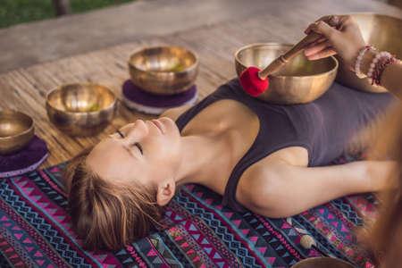 Nepal Boeddha koperen klankschaal bij spa salon. Jonge mooie vrouw doet massagetherapie klankschalen in de Spa tegen een waterval. Geluidstherapie, recreatie, meditatie, gezonde levensstijl en lichaamsverzorgingsconcept