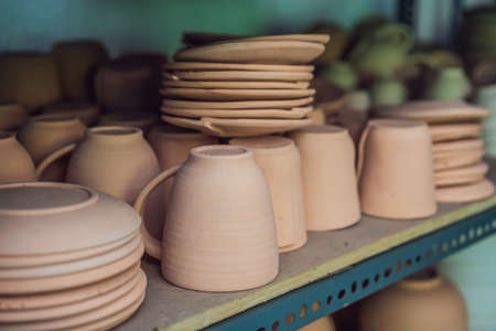 Cups on the shelves in the pottery workshop