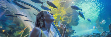 Young woman touches a stingray fish in an oceanarium tunnel BANNER, LONG FORMAT