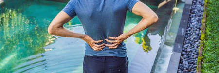 Men's back hurts against the backdrop of the pool. Pool helps with back pain. BANNER, LONG FORMAT Stok Fotoğraf