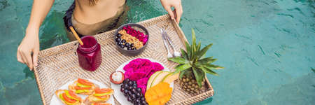 BANNER, LONG FORMAT Breakfast tray in swimming pool, floating breakfast in luxury hotel. Girl relaxing in the pool drinking smoothies and eating fruit plate, smoothie bowl by the hotel pool. Exotic summer diet. Tropical beach lifestyle. Bali Trend. Standard-Bild