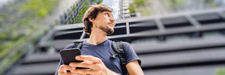 man using map app on smartphone on the background of skyscrapers BANNER, LONG FORMAT