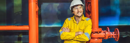 Young man in a yellow work uniform, glasses and helmet in industrial environment,oil Platform or liquefied gas plant BANNER, LONG FORMAT