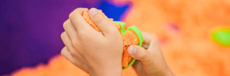 The boy's hands are playing with orange kinetic sand. BANNER, LONG FORMAT