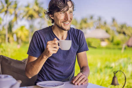 Man with a cup of tea on the cafe veranda near the rice terraces on Bali, Indonesia Stock Photo