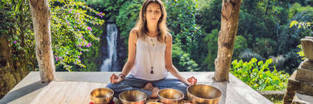 Woman playing on Tibetan singing bowl while sitting on yoga mat against a waterfall. Vintage tonned. Beautiful girl with mala beads meditating BANNER, LONG FORMAT
