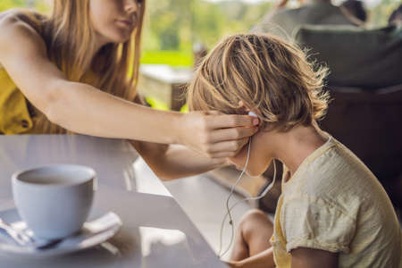 Mom puts her son in headphones in a cafe