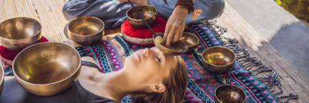 BANNER, LONG FORMAT Nepal Buddha copper singing bowl at spa salon. Young beautiful woman doing massage therapy singing bowls in the Spa against a waterfall. Sound therapy, recreation, meditation, healthy lifestyle and body care concept