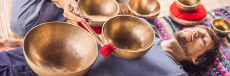 BANNER, LONG FORMAT Nepal Buddha copper singing bowl at spa salon. Young beautiful man doing massage therapy singing bowls in the Spa against a waterfall. Sound therapy, recreation, meditation, healthy lifestyle and body care concept