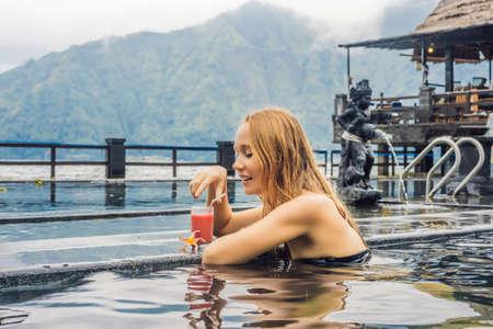 Geothermisches Spa. Frau, die sich im Thermalbad gegen den See entspannt. Konzept der heißen Quellen. Guavensaft trinken Standard-Bild