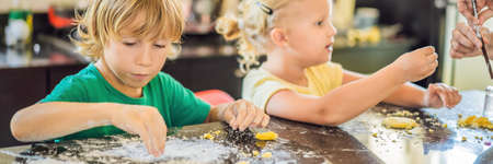 Two children a boy and a girl make cookies from dough BANNER, LONG FORMAT