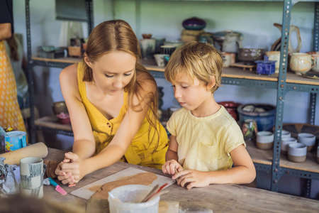 mother and son doing ceramic pot in pottery workshop