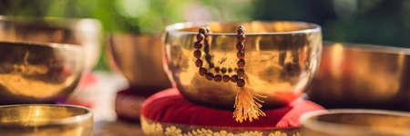 Tibetan singing bowls on a straw mat BANNER, LONG FORMAT