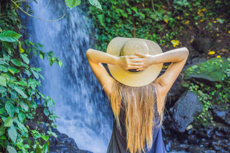 Woman traveler on a waterfall background. Ecotourism concept