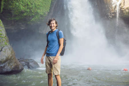 Man traveler on a waterfall background. Ecotourism concept