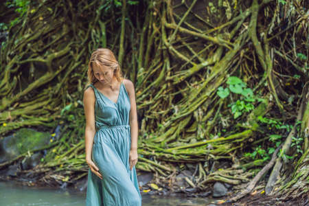 Young woman traveler in a Balinese garden overgrown with moss. Travel to Bali concept