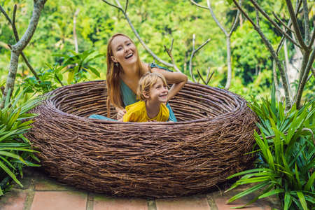 Bali trend, straw nests everywhere. Happy family enjoying their travel around Bali island, Indonesia. Making a stop on a beautiful hill. Photo in a straw nest, natural environment. Lifestyle. Traveling with kids concept. What to do with children. Child friendly place Stockfoto