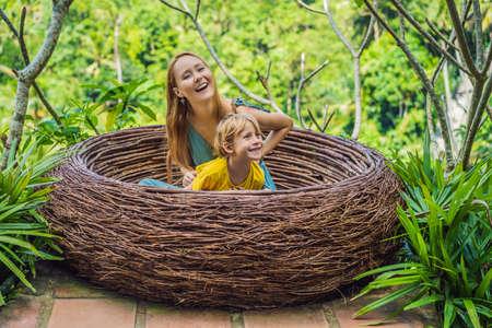 Tendance Bali, des nids de paille partout. Famille heureuse profitant de leur voyage autour de l'île de Bali, en Indonésie. Faire une halte sur une belle colline. Photo dans un nid de paille, milieu naturel. Mode de vie. Voyager avec le concept d'enfants. Que faire avec les enfants. Endroit adapté aux enfants