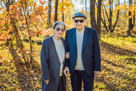 Pensioners in sunglasses in the autumn forest. Pensioners like gangsters