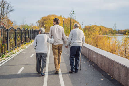 An elderly couple walks in the park with a male assistant or adult grandson. Caring for the elderly, volunteering Stock Photo