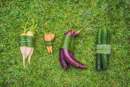Eco-friendly product packaging concept. Vegetables wrapped in a banana leaf, as an alternative to a plastic bag. Zero waste concept. Alternative packaging