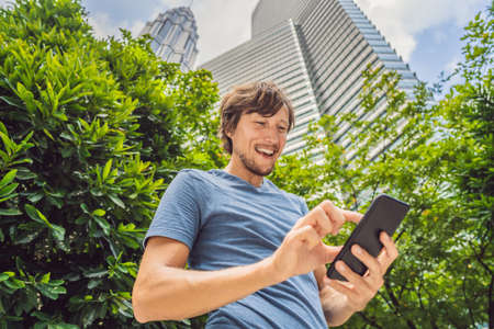 Man Tourist using navigation app on the mobile phone.