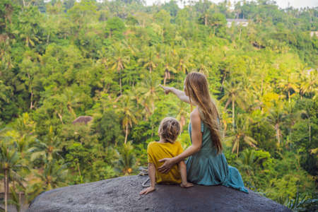 Mom and son tourists on a stone over the jungle. Stock fotó - 129825652
