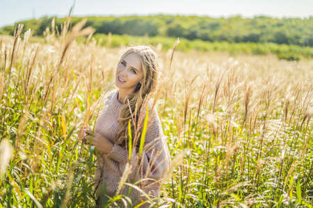 Young beautiful woman in autumn landscape with dry flowers, wheat spikes