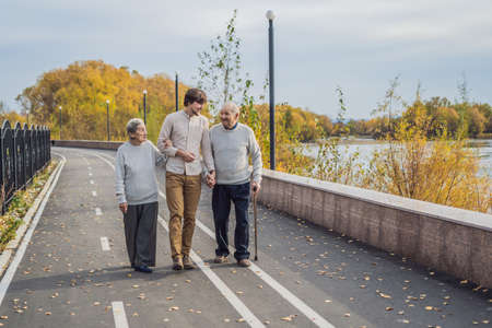 An elderly couple walks in the park with a male assistant or adult grandson 版權商用圖片