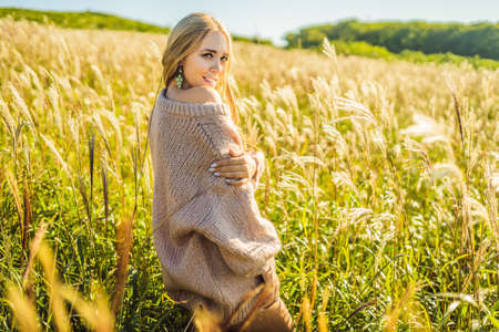Young beautiful woman in autumn landscape with dry flowers, wheat spikes.