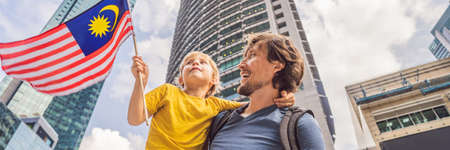 Dad and son tourists in Malaysia with the flag of Malaysia near the skyscrapers. Stockfoto