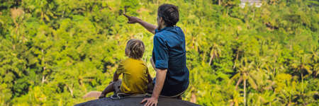 Dad and son tourists on a stone over the jungle. Traveling with kids concept. Stok Fotoğraf