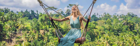 Young woman swinging in the jungle rainforest of Bali island, Indonesia.