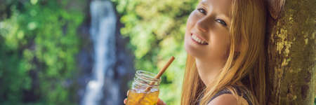 Closeup portrait image of a beautiful woman drinking ice tea with feeling happy in green nature and waterfall garden