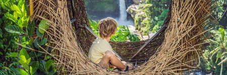 Boy tourist enjoying in straw nest Stock fotó