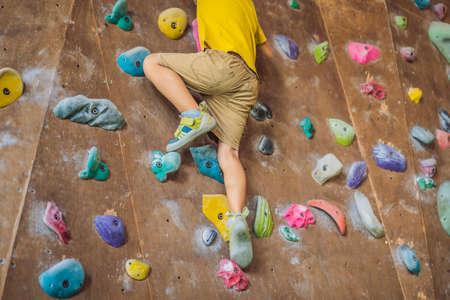 little boy climbing a rock wall in special boots. indoor Standard-Bild