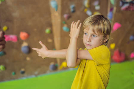 The boy is warming up before climbing a rock wall indoor