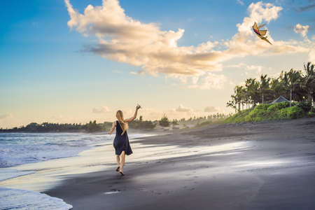 A young woman launches a kite on the beach. Dream, aspirations, future plans Archivio Fotografico