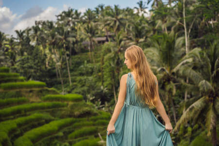 Beautiful young woman walk at typical Asian hillside with rice farming, mountain shape green cascade rice field terraces paddies. Ubud, Bali, Indonesia. Bali travel concept